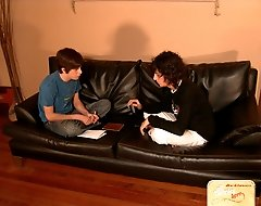 Two cute twinks throwing dice on a leather couch, French-kissing and undressing one another